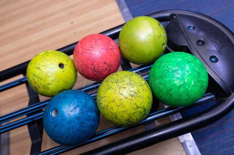 Close - up of colorful bowling balls. Bowling alley was laid in a wooden lane in the bowling hall. Colorful bowling balls in return machine. Multicolored bowling royalty free stock images