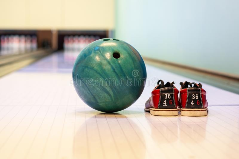 Close-up colorful bowling balls and bowling pins and bowling shoes on the bowling track. Game and Fun stock photos