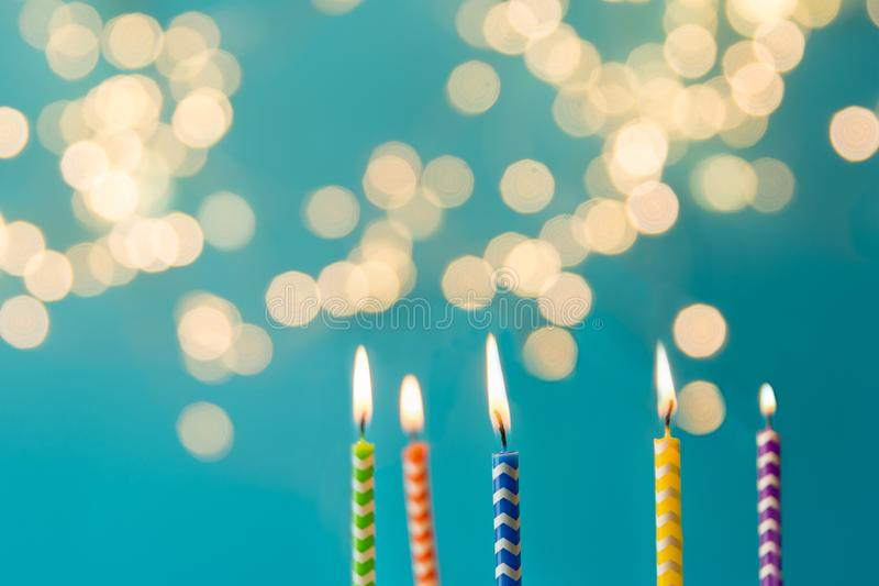 Close up colorful candles on blue background against defocused light. Holiday celebration concept. Copy space.  stock photography