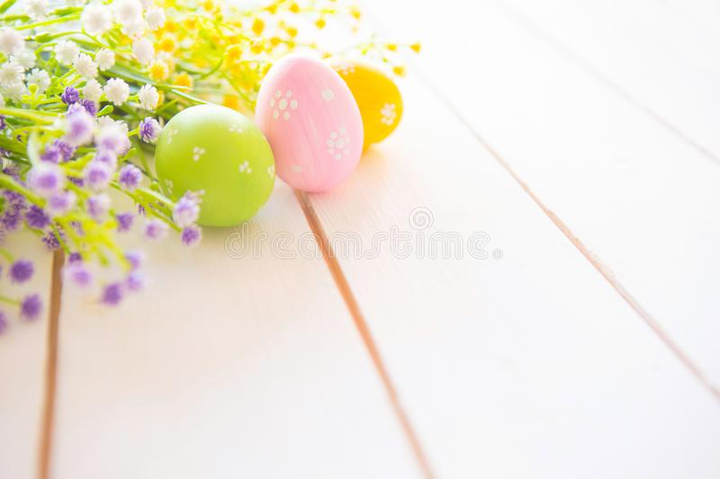 Colorful easter eggs with flowers on white wooden table stock photography