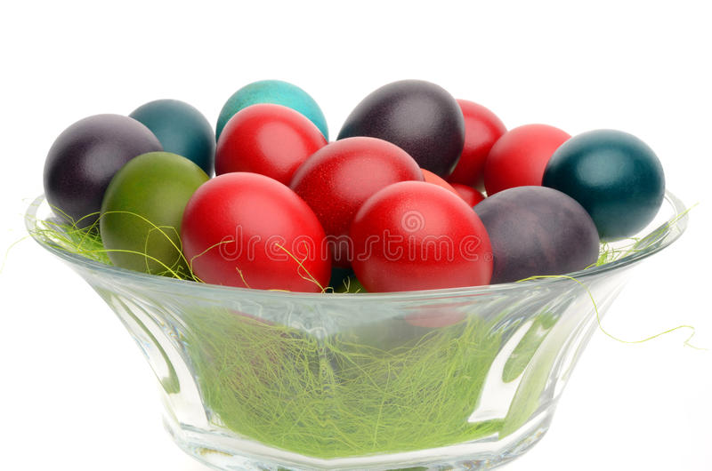 Close up on colorful hand dyed easter eggs in a glass bowl decorated with grass. stock images