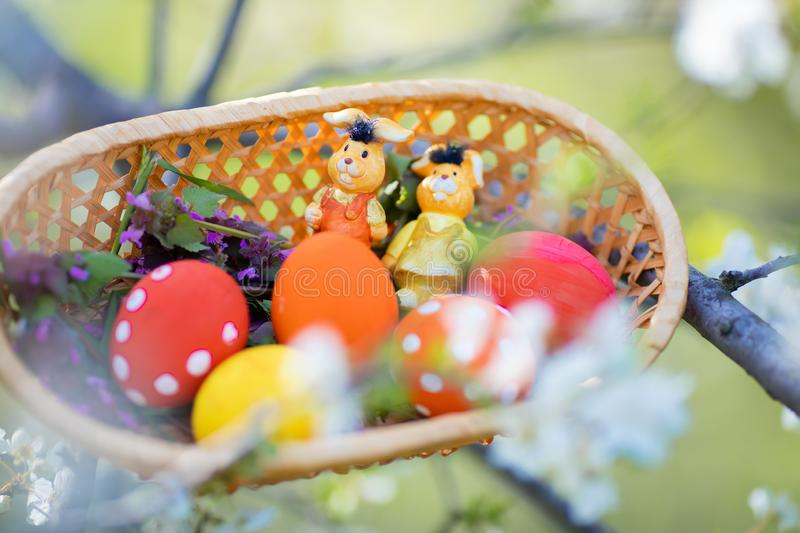 Close-up of colorful hand made Easter eggs and little bunnies figurines in a basket outdoors royalty free stock photography