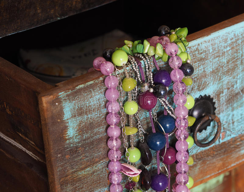 Close up colorful jewellery in old painted wooden drawer stock photos