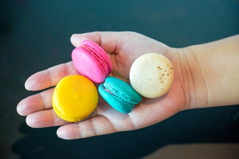 Close up colorful macarons dessert with vintage toneson hand. Colorful french macarons background,Different colorful macaroons bac stock image
