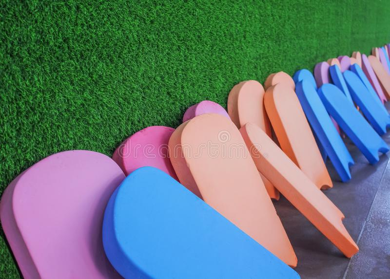 Colorful multicolored stack old kick board on artificial green grass wall background. Close up Colorful multicolored stack old kick board on artificial green royalty free stock image
