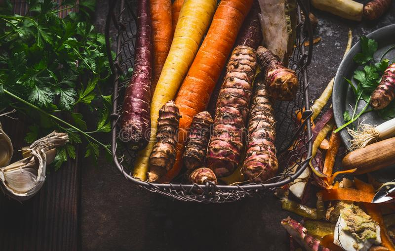 Close up of colorful organic root vegetables in harvest basket on dark background, top view. Healthy and clean food and eating stock image
