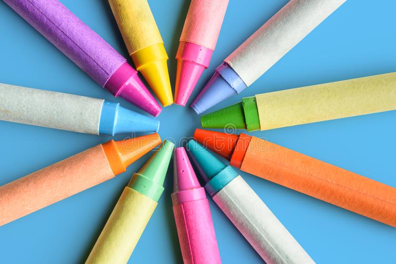 Close up of colorful pastel crayons on blue background stock photo