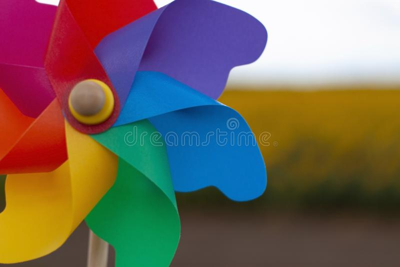 Color pinwheel toy against summer sky. Close-up colorful pinwheel in a garden. color pinwheel toy in sunny summer day royalty free stock photos