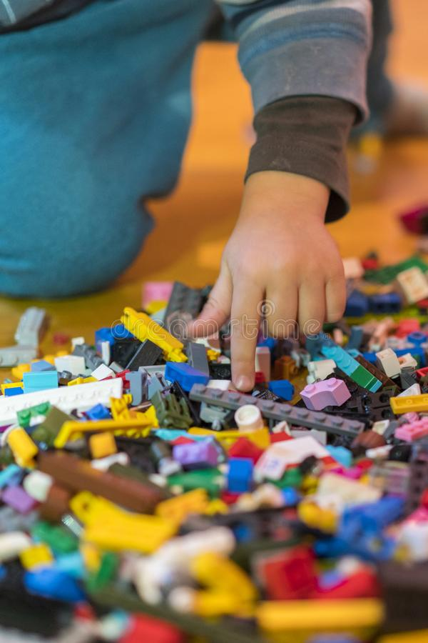 Close up of colorful plastic bricks on the floor. Early learning. Children's plastic constructor on the floor. Children's hands stock image
