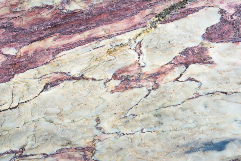 Close up of colorful rock surface, natural background, pattern and texture. Metamorphic white quartzite folded and fractured. Together with red coarse sandstone stock image