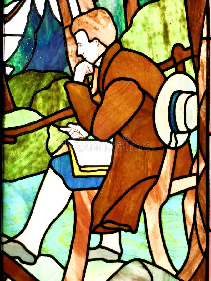 Stained glass. Close-up on a colorful stained glass representing a man reading and thinking royalty free stock photo