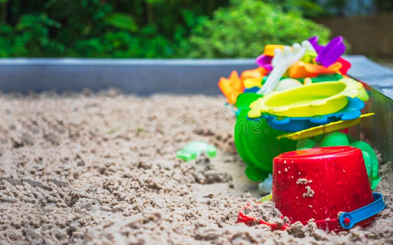 Close up of colorful toys on sand playground. Sandbox and set of color plastic toys royalty free stock image