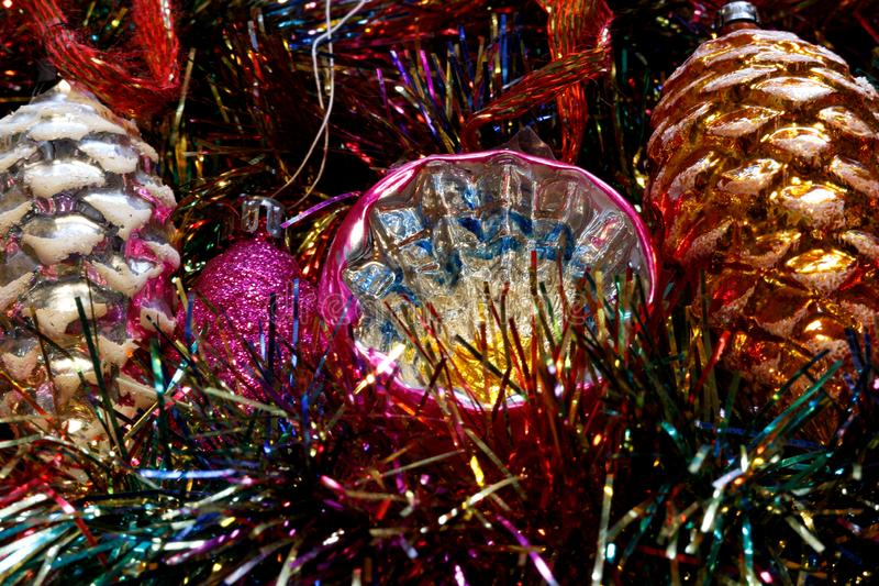 Vintage Christmas tree decorations on a bed of glitter. Close up on colorful vintage Christmas tree ornaments on a bed of glitter in different colors. Retro stock photo
