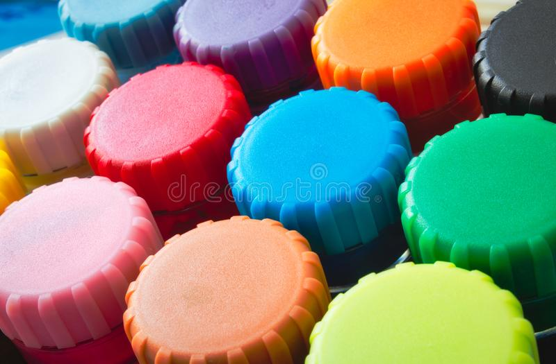 Close-up of colourful lids of kids` poster paint pots. Close-up of colorful lids of kids` poster paint pots for arts and crafts royalty free stock image