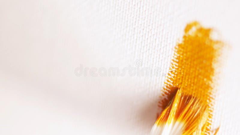 Close-up com do grande desenho de escova branco a linha pela pintura de óleo alaranjado na lona branca a??o Artes e fotos de stock royalty free