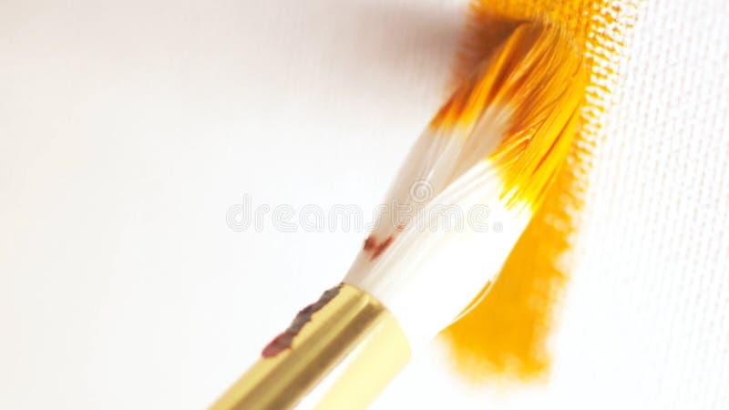 Close-up com do grande desenho de escova branco a linha pela pintura de óleo alaranjado na lona branca a??o Artes e fotos de stock