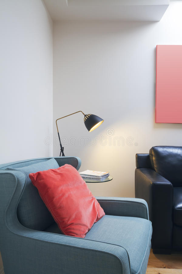 Close up of comfortable reading nook in contemporary home. With lamp on side table royalty free stock image