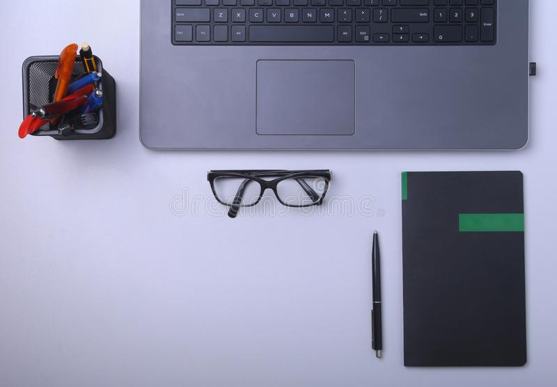 Close-up of comfortable working place in office with laptop, notebook, glasses, pen and other equipment laying on table. With copy space. Top view royalty free stock photos