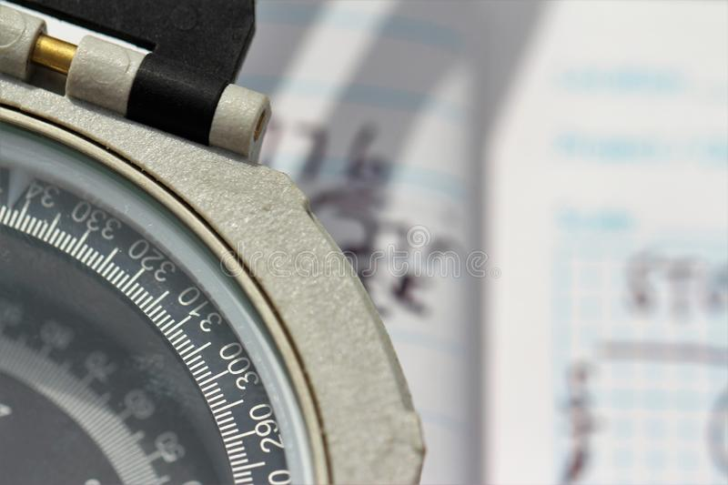 Close-up of a compass dial in front of a hand-written field notebook stock image