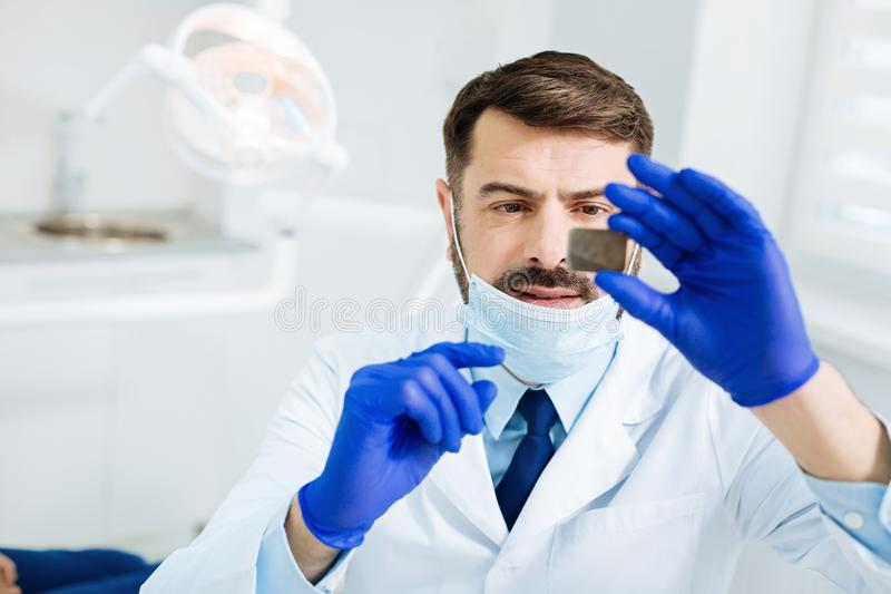 Close up of concentrated dentist with Xray image stock images