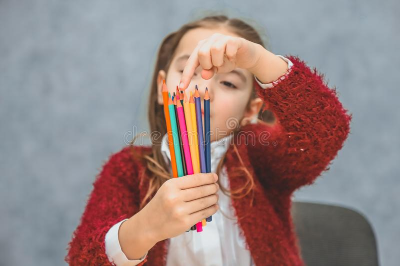 Close-up concept of colored pencils in one hand girls. Keeping them selects the right pencil. The gray background. The stock photo
