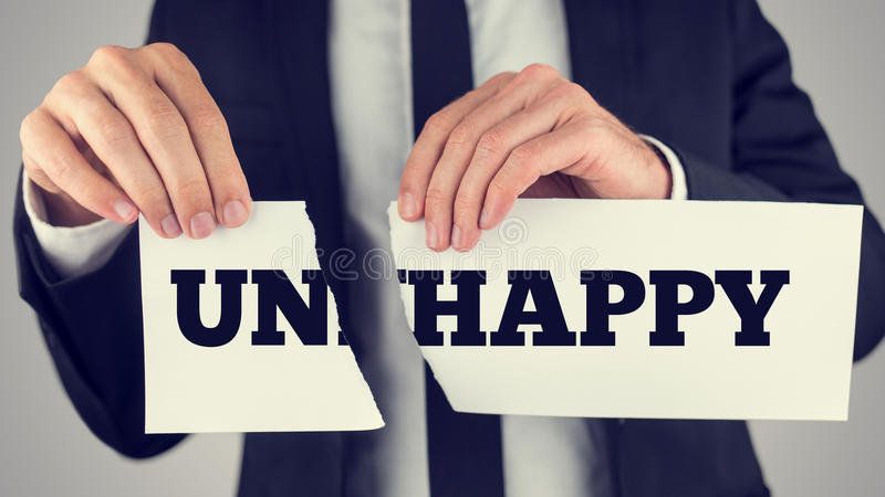 Close up Conceptual Businessman Tearing a White Paper with Unhappy - Happy Message Isolated on a Gray Background royalty free stock photo
