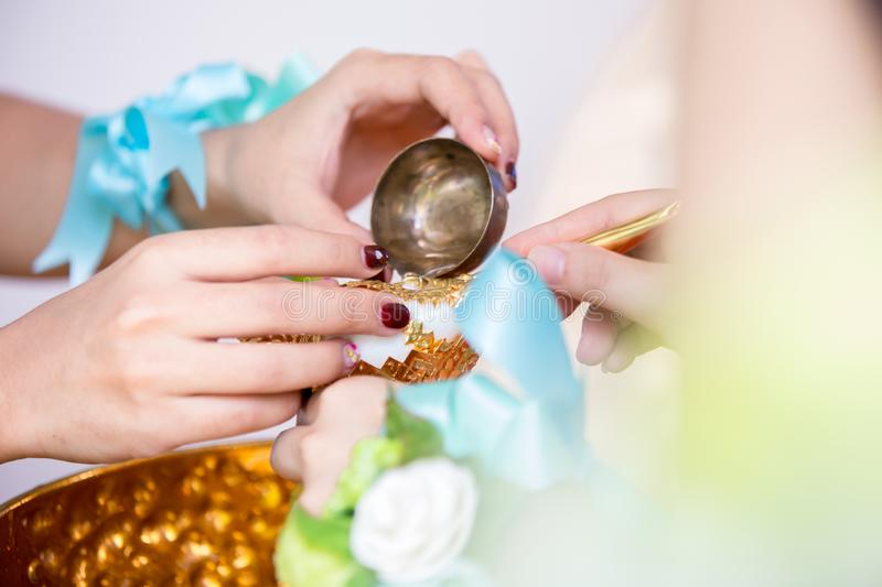 Close up conch shell in hand, wedding accessory for thai culture wedding ceremony with blur groom and bride on background. royalty free stock images