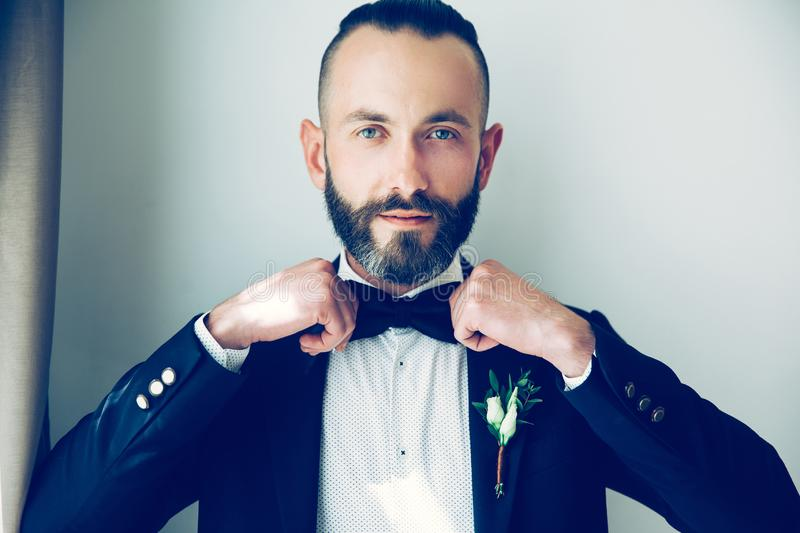 Close up. confident man straightening his bow tie. royalty free stock image