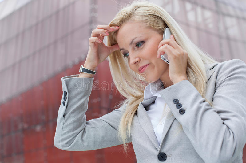 Close-up of confused businesswoman communicating on cell phone against office building stock photos