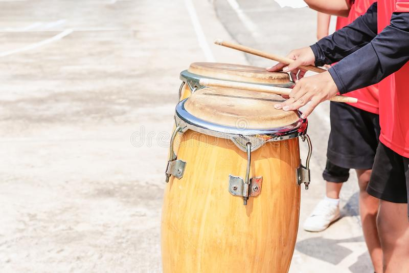 Close up of conga drums with man`s hands holding drumsticks set on concrete floor in a stadium for cheer. Close up of conga drums with man`s hands holding royalty free stock photo