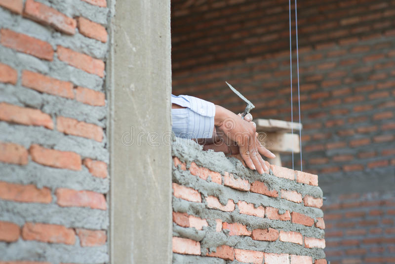 Close-up of construction process mason work with brick installation royalty free stock images