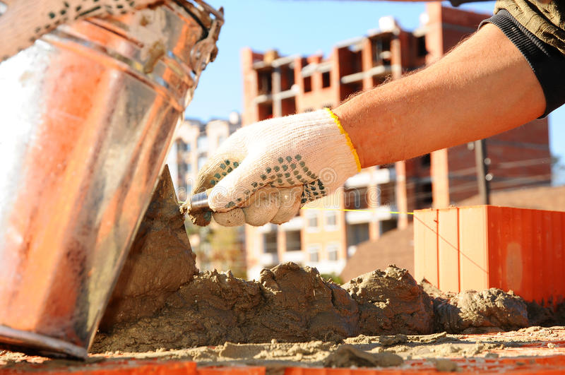 Close-up of construction process mason work with brick installation by trowel putty knife outdoors stock photos