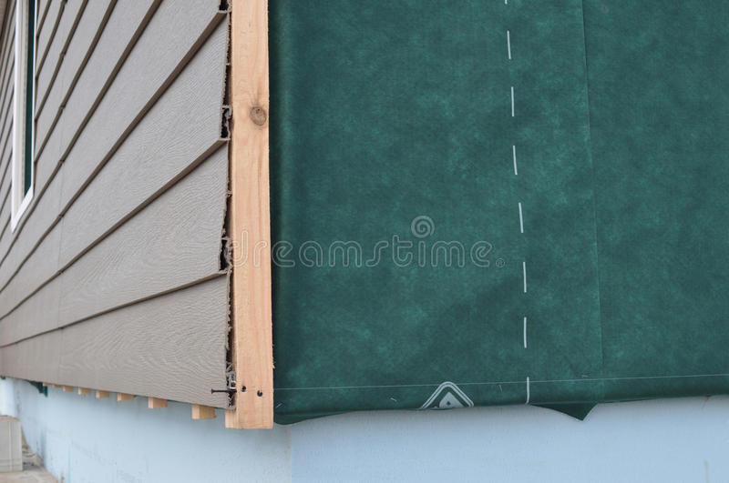 Close up on Construction or repair of the rural house,plastic siding, fixing facade, membrane, insulation house wall. royalty free stock image