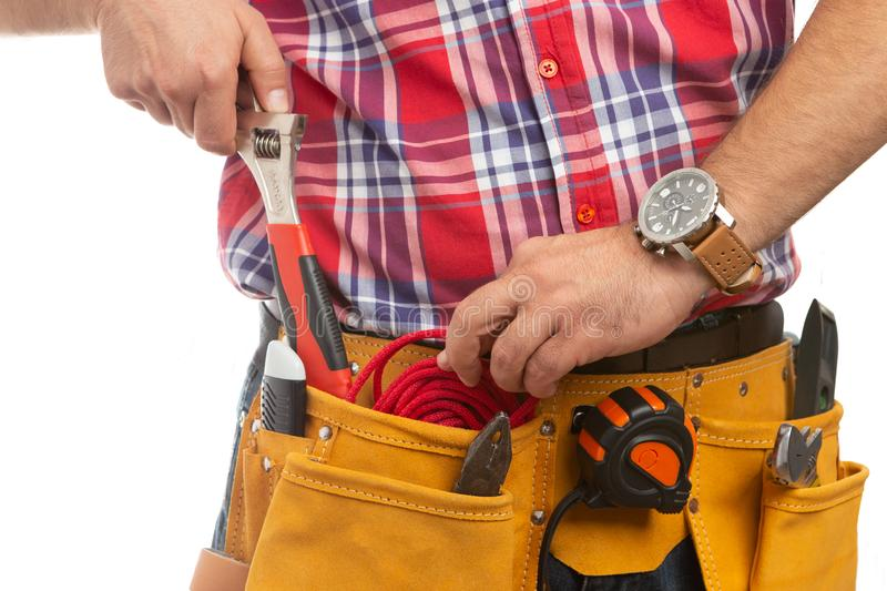 Close-up of construction worker putting rope in pocket. Close-up of male construction worker putting red rope back in pocket while holding wrench in hand with royalty free stock photos