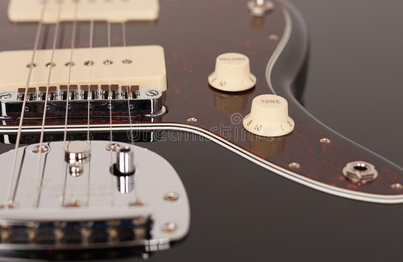 Close up of control tone  on  black electric guitar, studio shoot. Red tortoise shell pickguard, alder body, two single coil. Close up of control tone on black stock photography