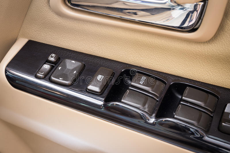 Close Up of controls button switch on the door. Interior detail. In luxury modern car royalty free stock photo