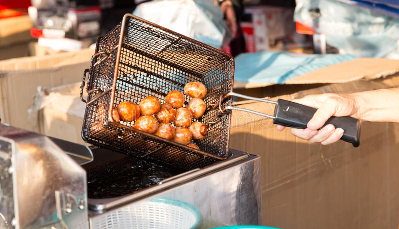 Close up of cook frying meatballs at street market. Cooking, asian kitchen and food concept - close up of cook frying meatballs in oil at street market royalty free stock photos