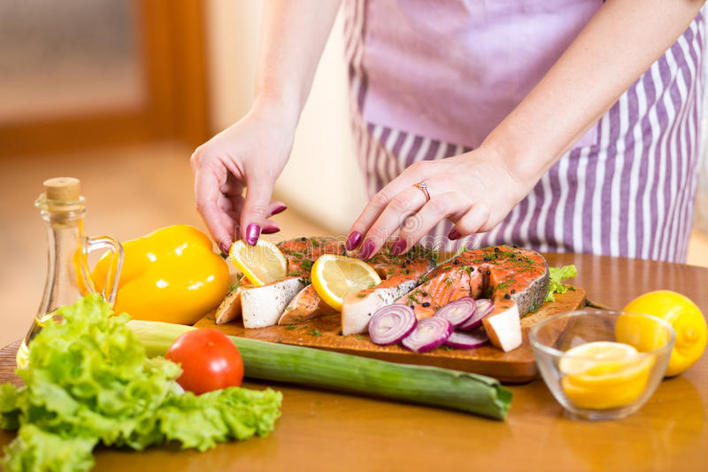 Close up cooking fish in domestic kitchen. Close up cooking salmon fish in domestic kitchen royalty free stock image