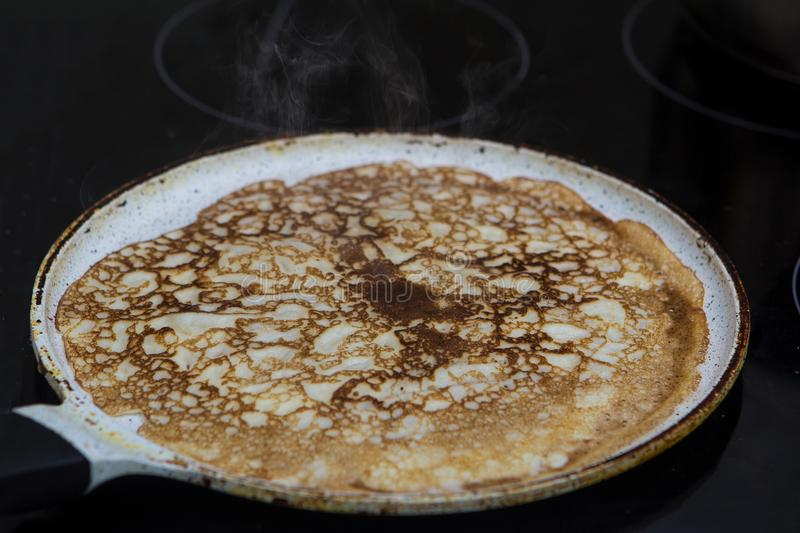 Close-up cooking pancakes in a frying pan with a wooden stick royalty free stock photography
