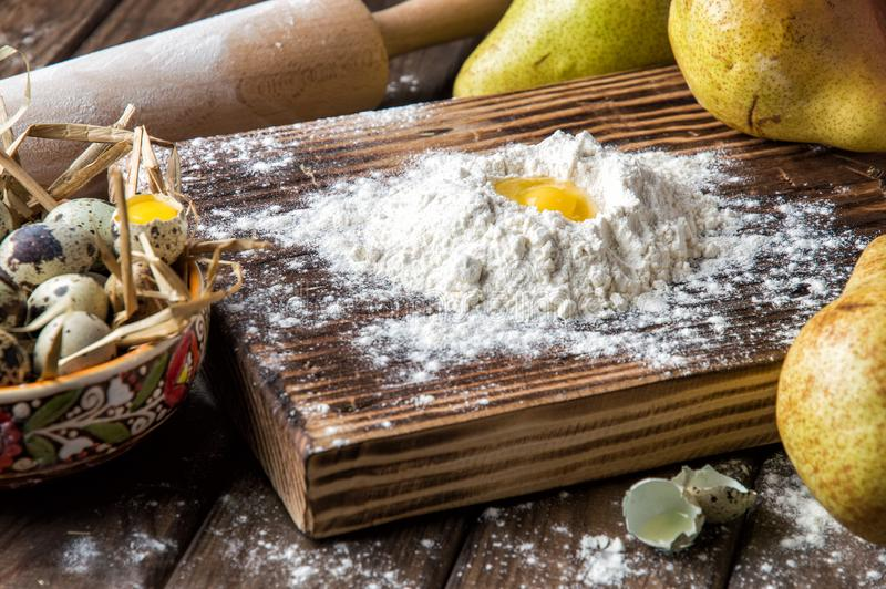 Close up. Cooking traditional pear cake. Making dough from quail eggs and flour on a brown wooden board royalty free stock photos