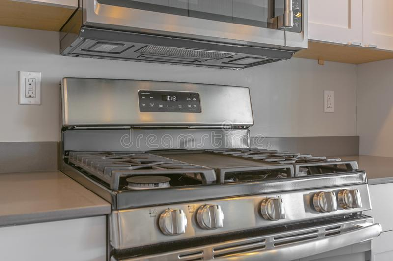Close up of the cooktop of a range under wall mounted microwave inside a kitchen. The gray wall of this room is lined with built in wooden cabinets royalty free stock image