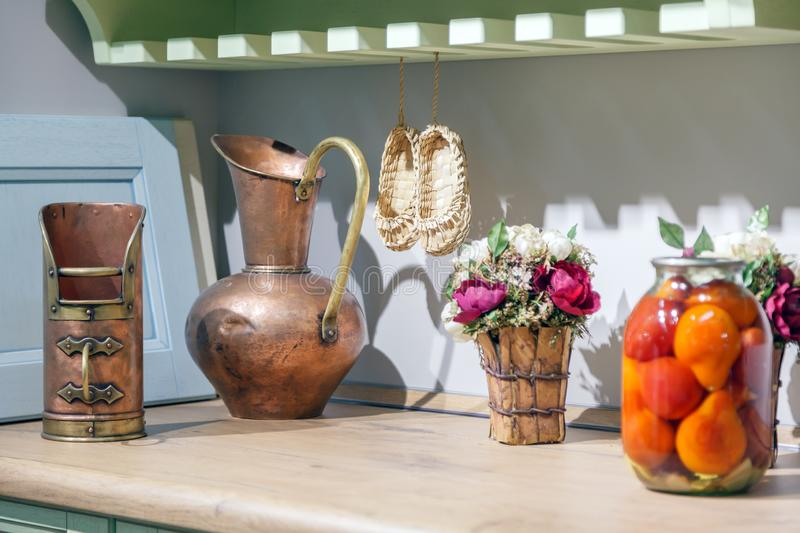 Close-up of a copper antique oriental jug, an iron vintage mug, a wooden vase with flowers and a glass jar with salted tomatoes on stock image