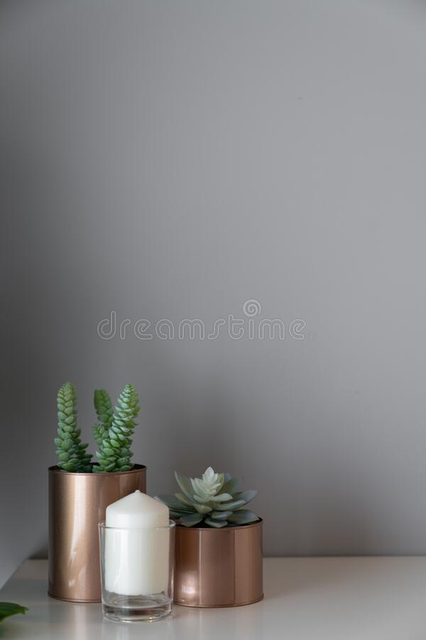 Free Close Up  Copper Vase  With Artificial Plant Inside And White Candle In Glass On Cream Spray-painted Working Table With  Gray Pain Stock Images - 169149244