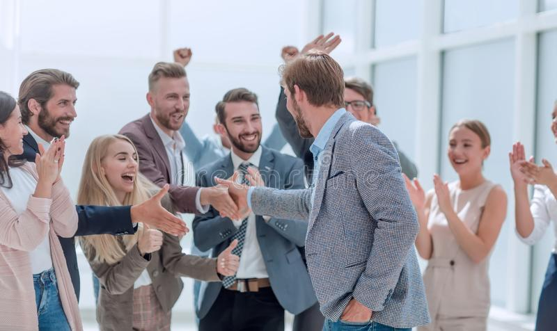 Corporate group of employees congratulating their colleague. royalty free stock image