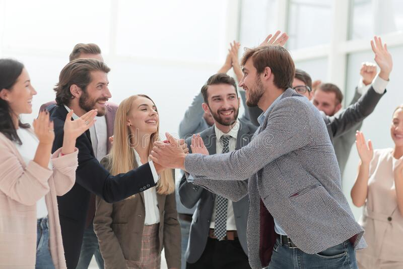 Corporate group of employees congratulating their colleague. stock photo