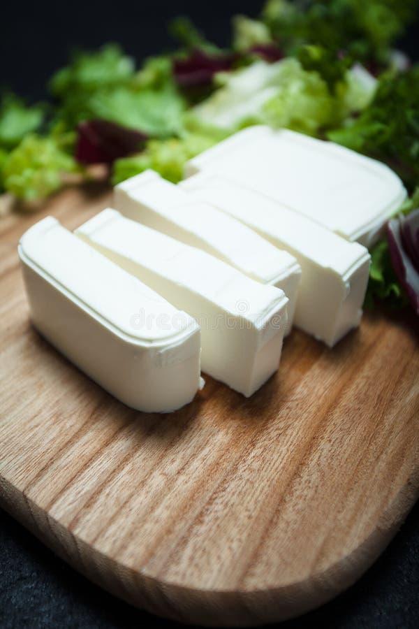 Close-up cortado em uma placa de corte de madeira, folhas do queijo de feta da alface fotografia de stock