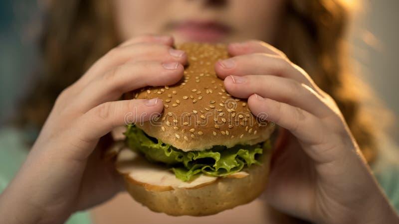 Close up cortante fêmea do hamburguer do fast food, nutrição insalubre e comer demais fotos de stock royalty free