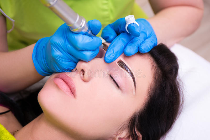Close up of cosmetologist applying permanent make up on eyebrows royalty free stock images