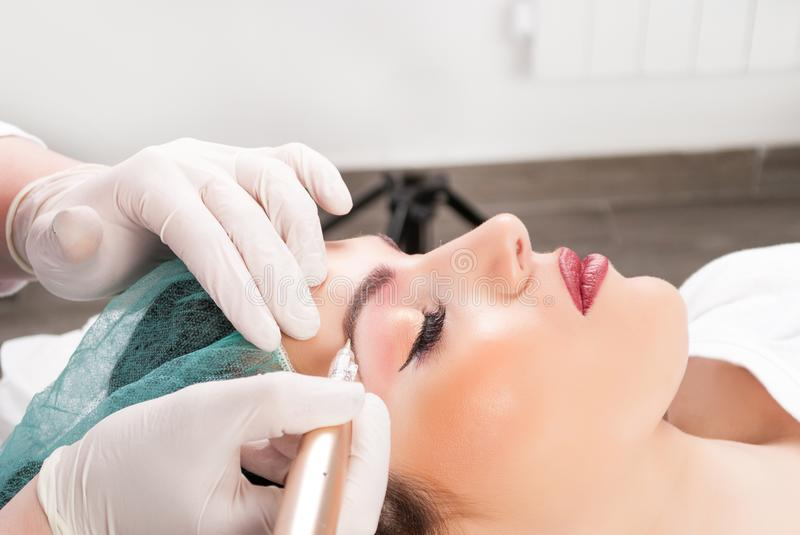 Close up of cosmetologist applying permanent make up on female eyebrows stock photo