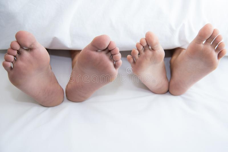 Close up of couple barefoot under blanket in bedroom in honeymoon vacation holiday in long weekend at home. Relaxation of sexual royalty free stock photos
